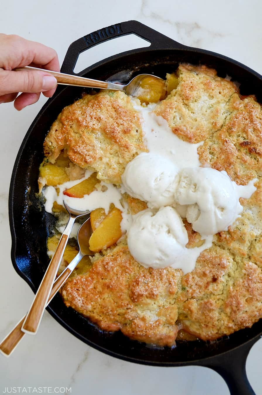 A skillet with peach cobbler and melting ice cream on top with spoons