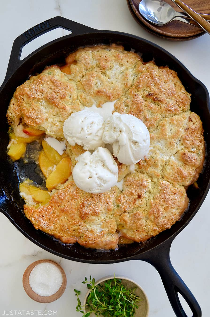 A cast-iron skillet containing peach cobbler with ice cream on top