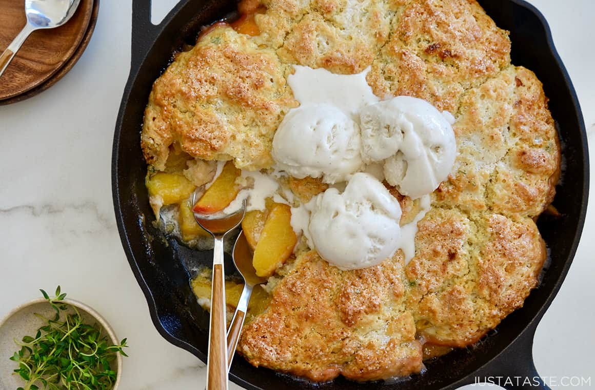 Peach cobbler in a cast-iron skillet with melting ice cream on top