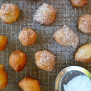 Apple Fritters dusted with powdered sugar on a wire cooling rack over a baking sheet.