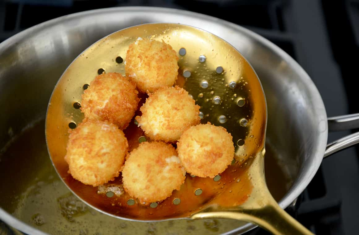 A spoon filled with goat cheese balls after they've been fried