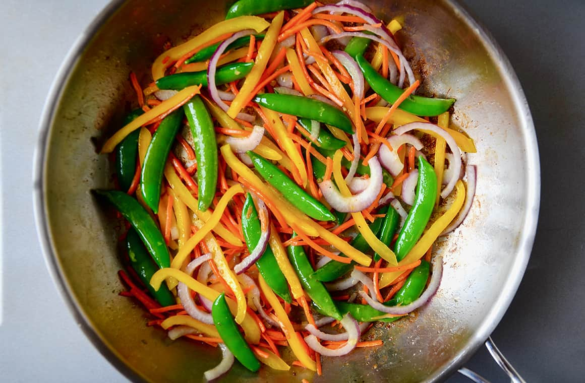 Vegetables in a stainless steel sauté pan