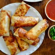 A white plate piled high with Air Fryer Egg Rolls next to small bowls containing sweet chili sauce and sliced scallions, and a plate with green lettuce topped with two egg rolls.