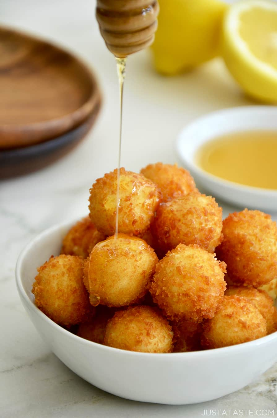 A white bowl containing fried goat cheese balls with honey drizzled on top