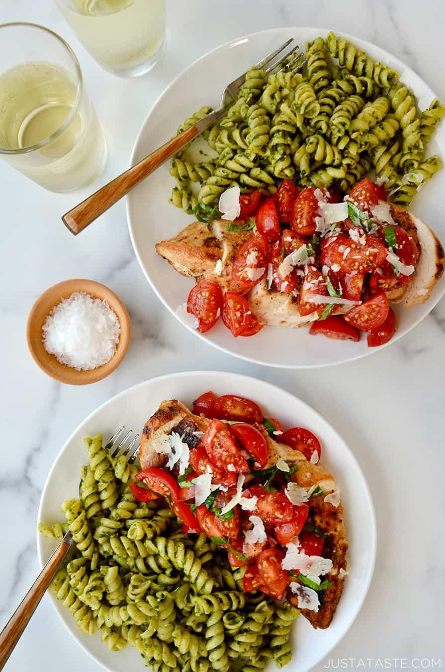 White plates containing bruschetta chicken and rotini pesto pasta