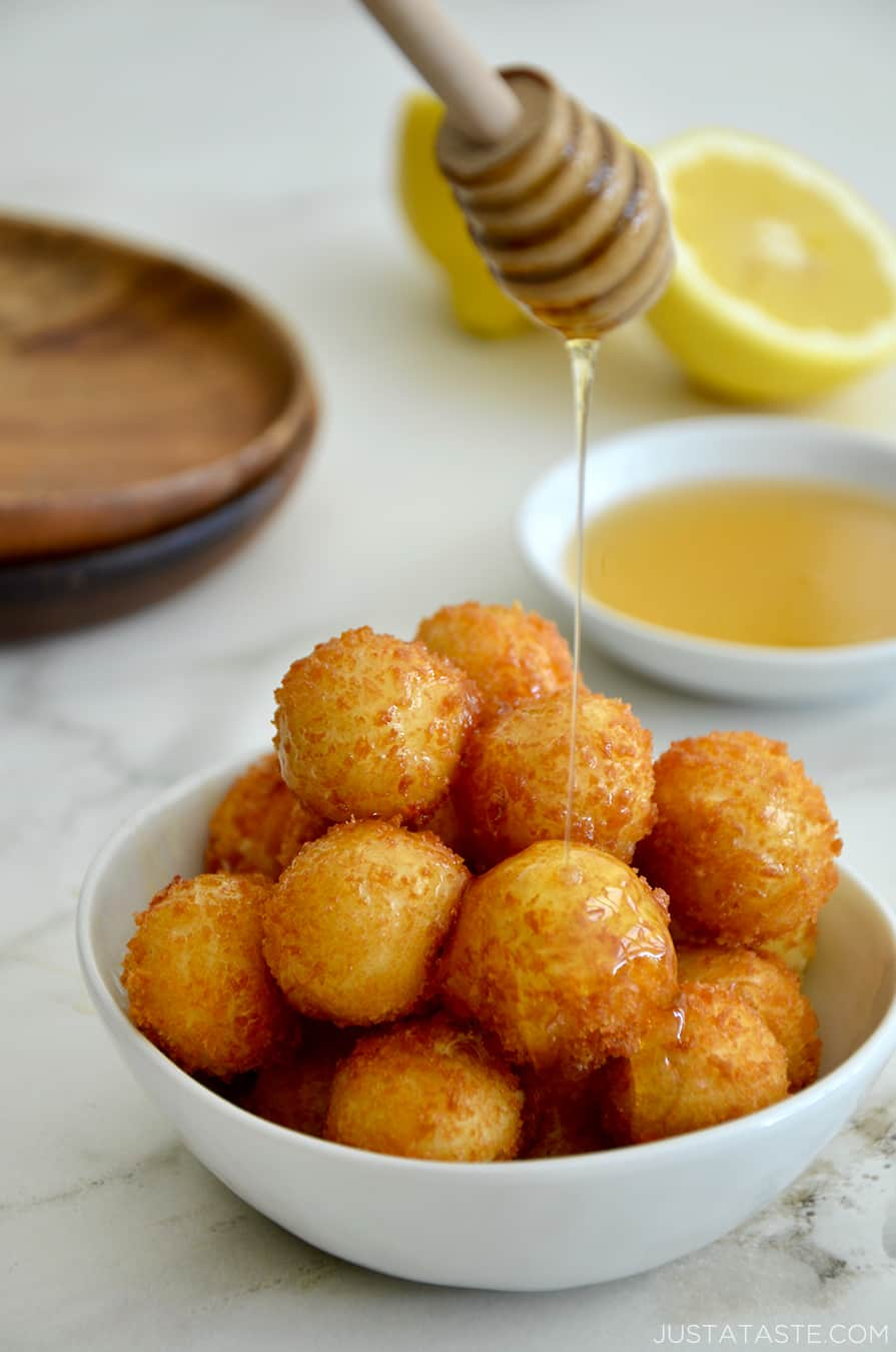 A bowl of fried goat cheese balls with lemon in the background