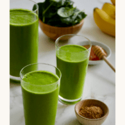 Three glasses filled with Healthy Green Smoothie mix next to a bowl containing fresh spinach and a smaller bowl containing ground flaxseed.