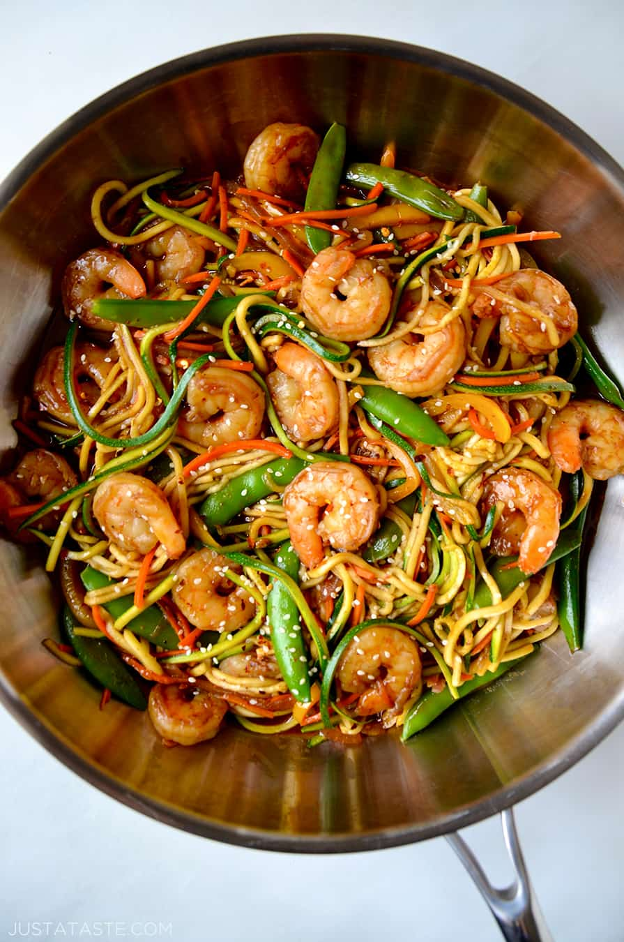 A top-down view of a skillet containing shrimp and vegetables