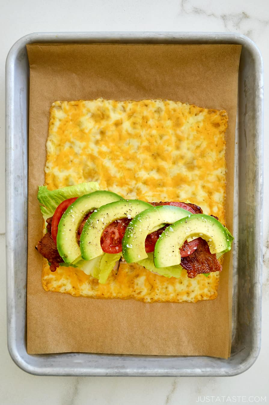 A top-down view of melted cheese sandwich wrap filled with turkey, bacon, avocado, lettuce and tomato