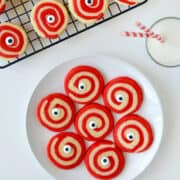 Monster Eye Halloween Cookies on a white plate next to a glass of milk and wire cooling rack containing more cookies.