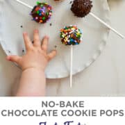 A child's hand reaching for No-Bake Chocolate Cookie Pops decorated with rainbow sprinkles on a white plate.