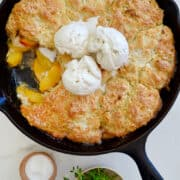 Peach Cobbler with buttermilk biscuits in a cast-iron skillet topped with three scoops of vanilla bean ice cream.