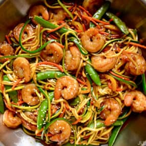 A top-down view of stir-fry with zucchini noodles and shrimp