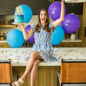 Kelly Senyei sitting on her kitchen counter throwing confetti into the air while holding a cake