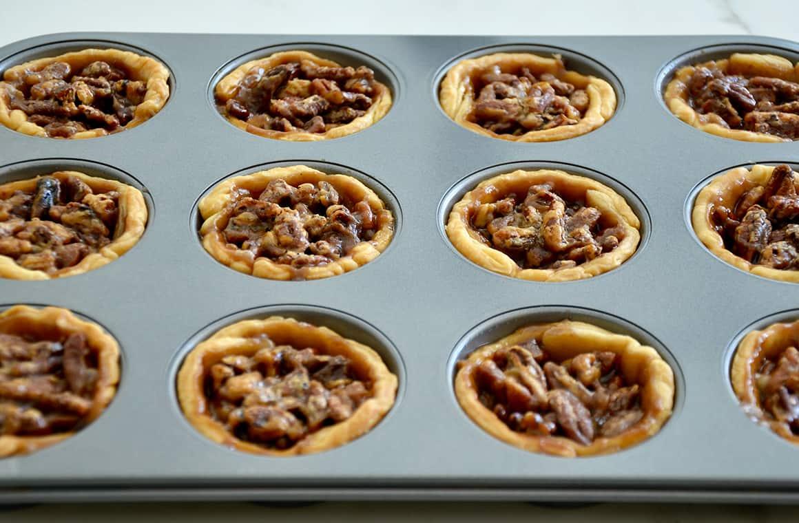 Freshly baked golden brown individual pecan pies