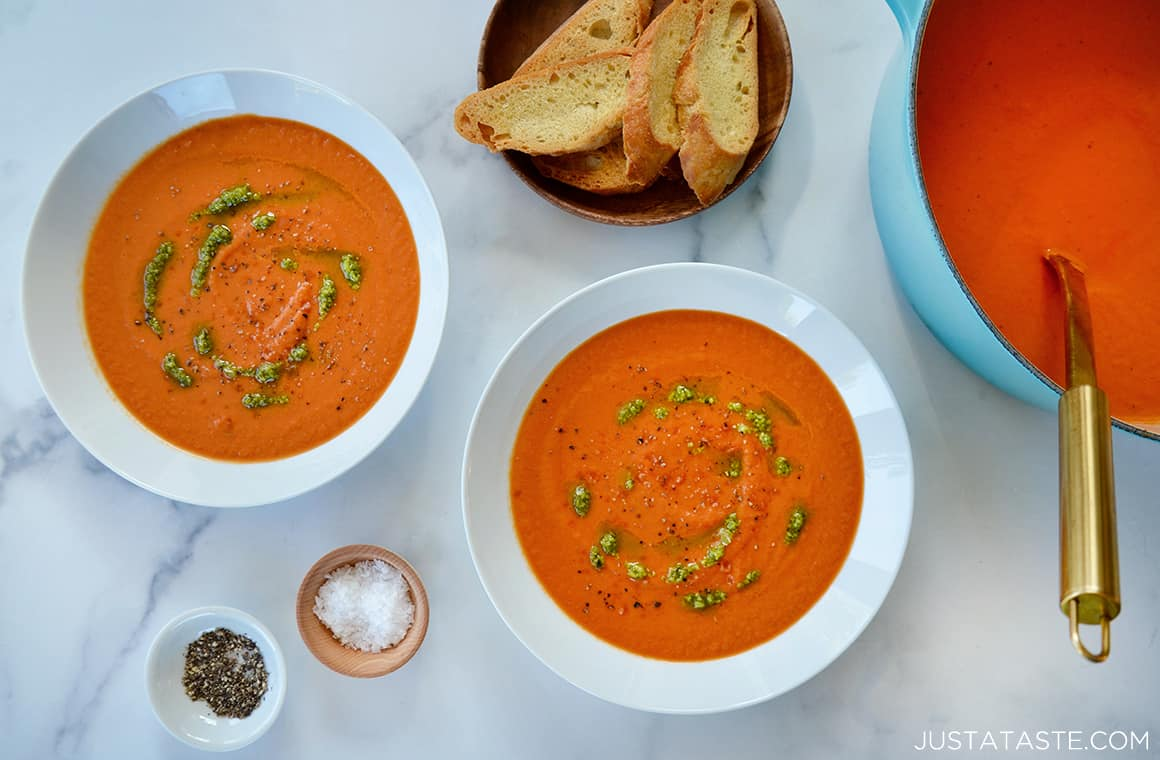White bowls containing tomato soup topped with basil drizzle