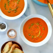 Two white bowls containing Creamy Homemade Tomato Soup drizzled with basil pesto next to a stockpot containing soup and small bowls containing black pepper, salt, and crusty toasts.