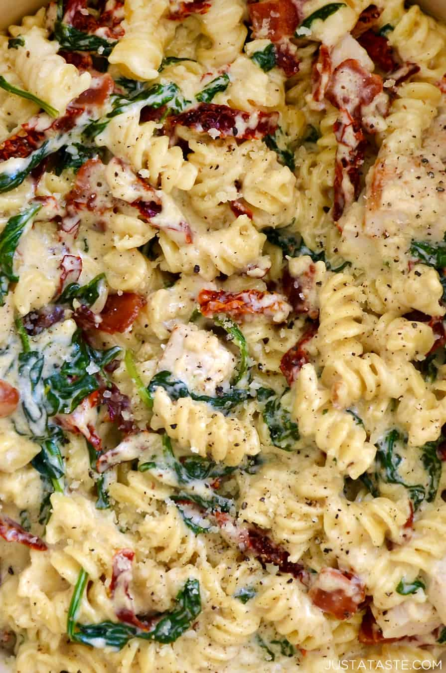 A close-up view of Creamy Tuscan Chicken Pasta with spinach and sun-dried tomatoes