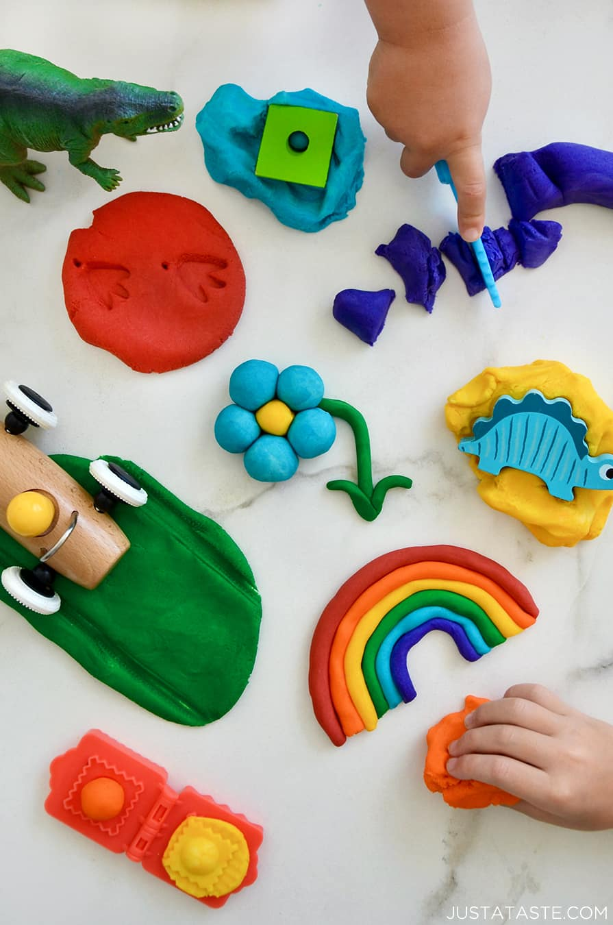 A top-down view of a rainbow of homemade playdough colors with toys