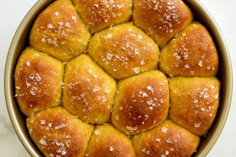 A top down view of pumpkin dinner rolls in a gold baking pan