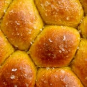 A close-up view of golden-brown Homemade Pumpkin Dinner Rolls topped with large-flake sea salt.
