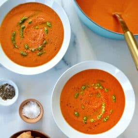 A teal stock pot of tomato soup with two white bowls filled with soup