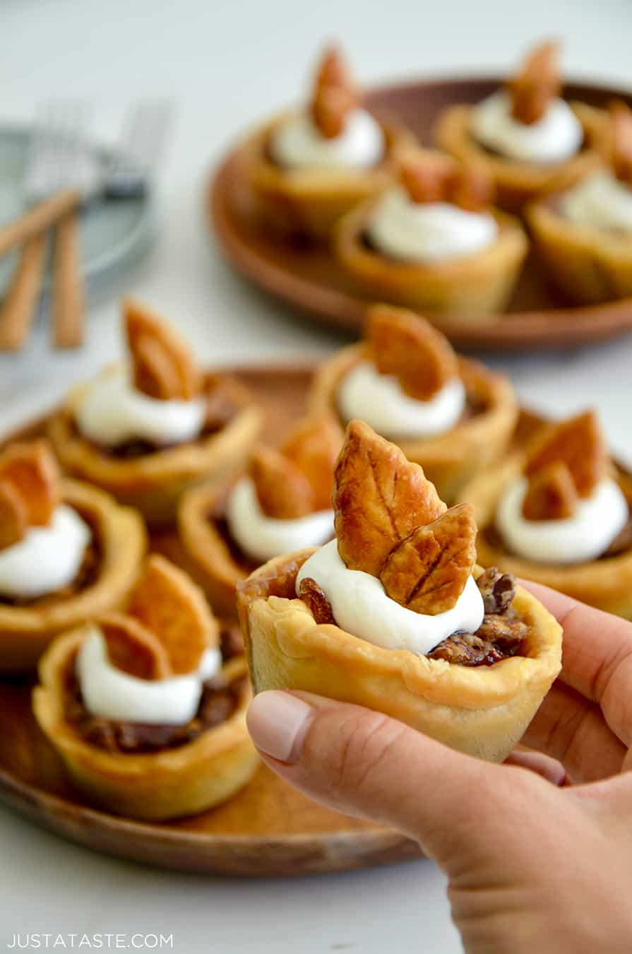A hand holding a Muffin Tin Mini Pecan Pies topped with whipped cream