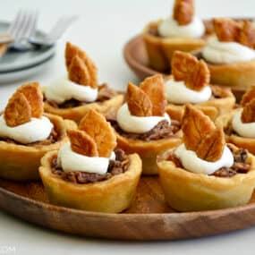 Individual mini pecan pies topped with whipped cream on serving plate