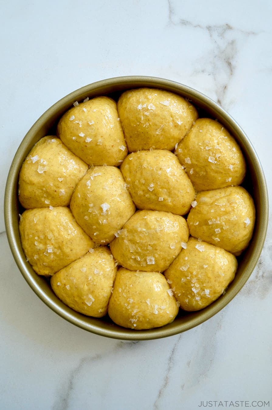 Unbaked dinner rolls in a gold baking pan