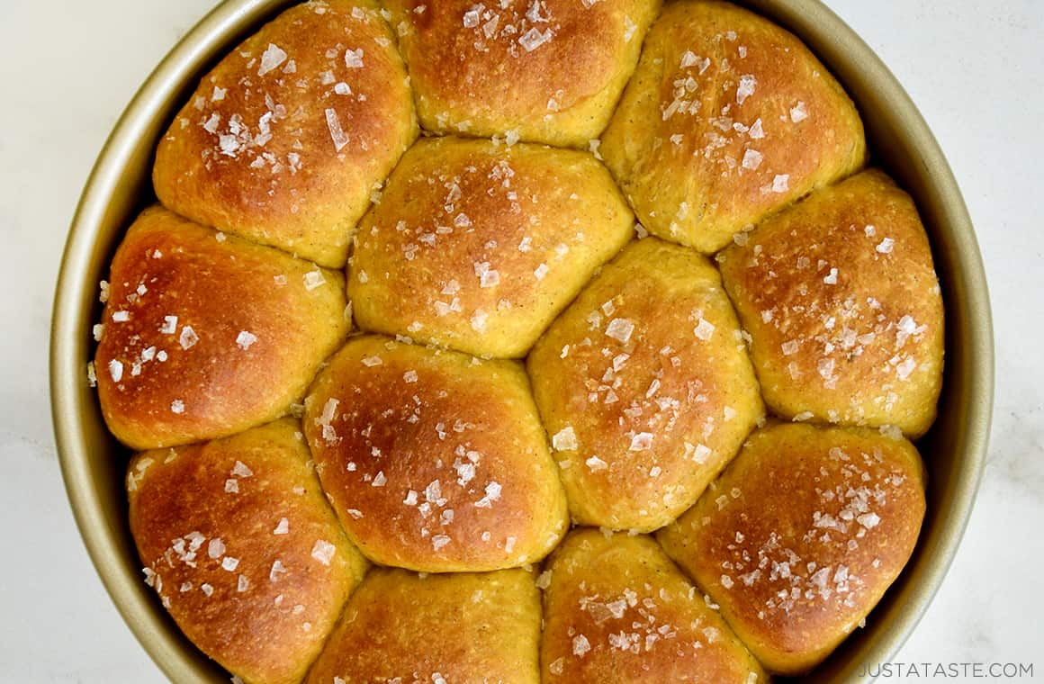 A top down view of baked dinner rolls topped with sea salt