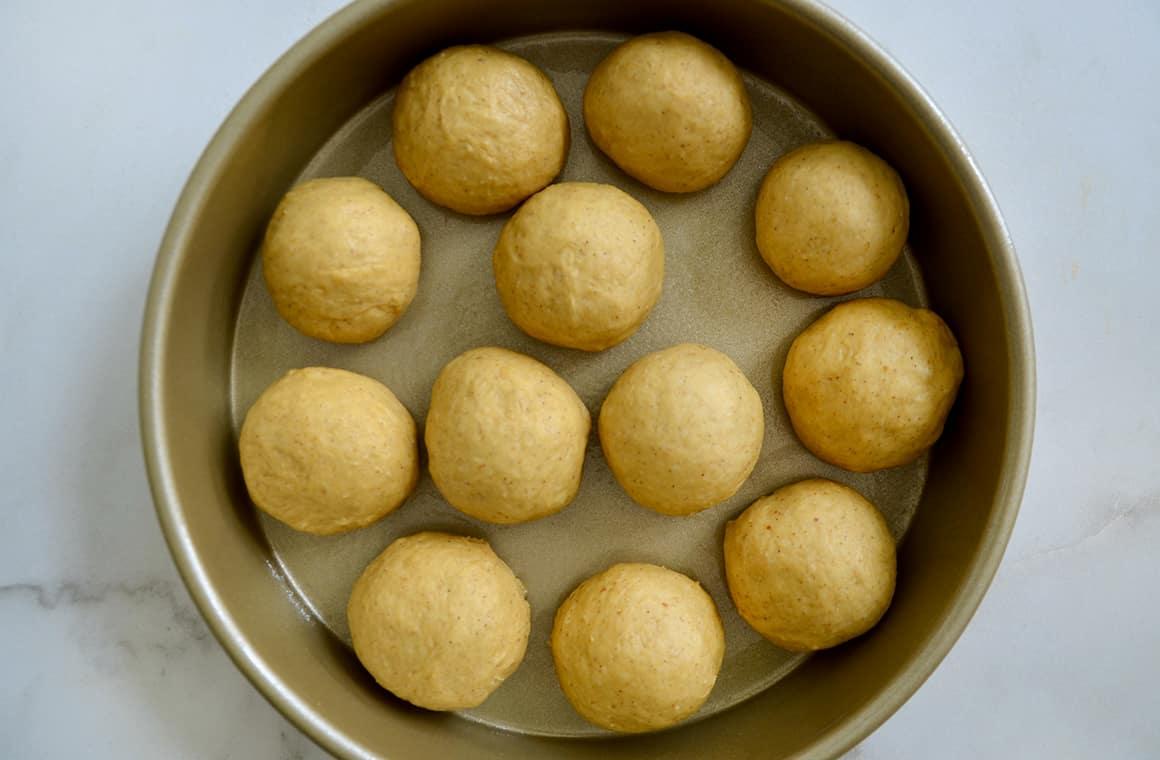 Circles of bread dough in a gold baking pan