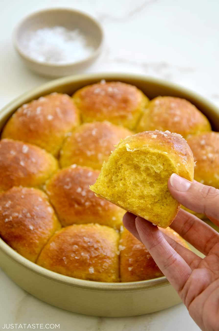 A hand holding a fluffy dinner roll with a baking pan in the background