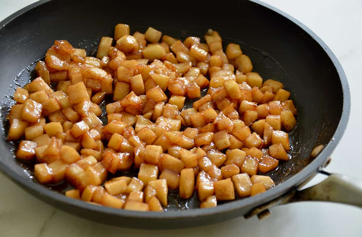 A large skillet containing diced sautéed apples