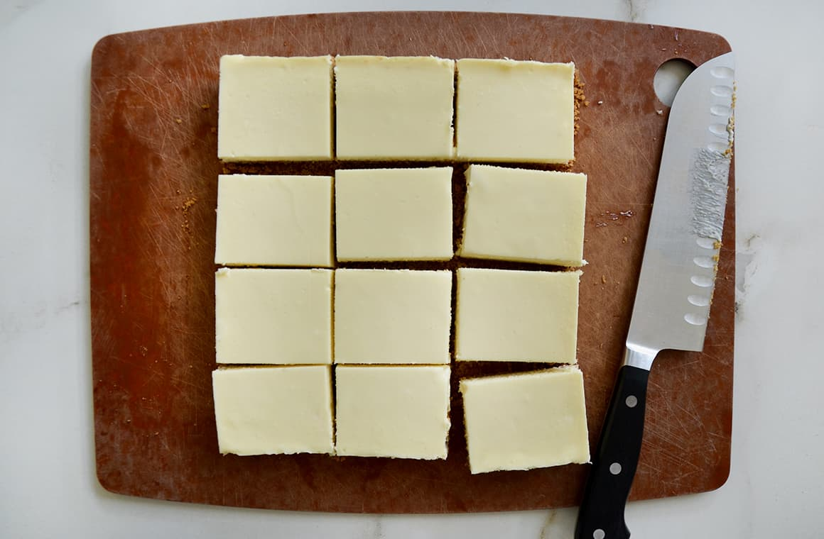 Sliced cheesecake bars next to a sharp knife on a wooden cutting board