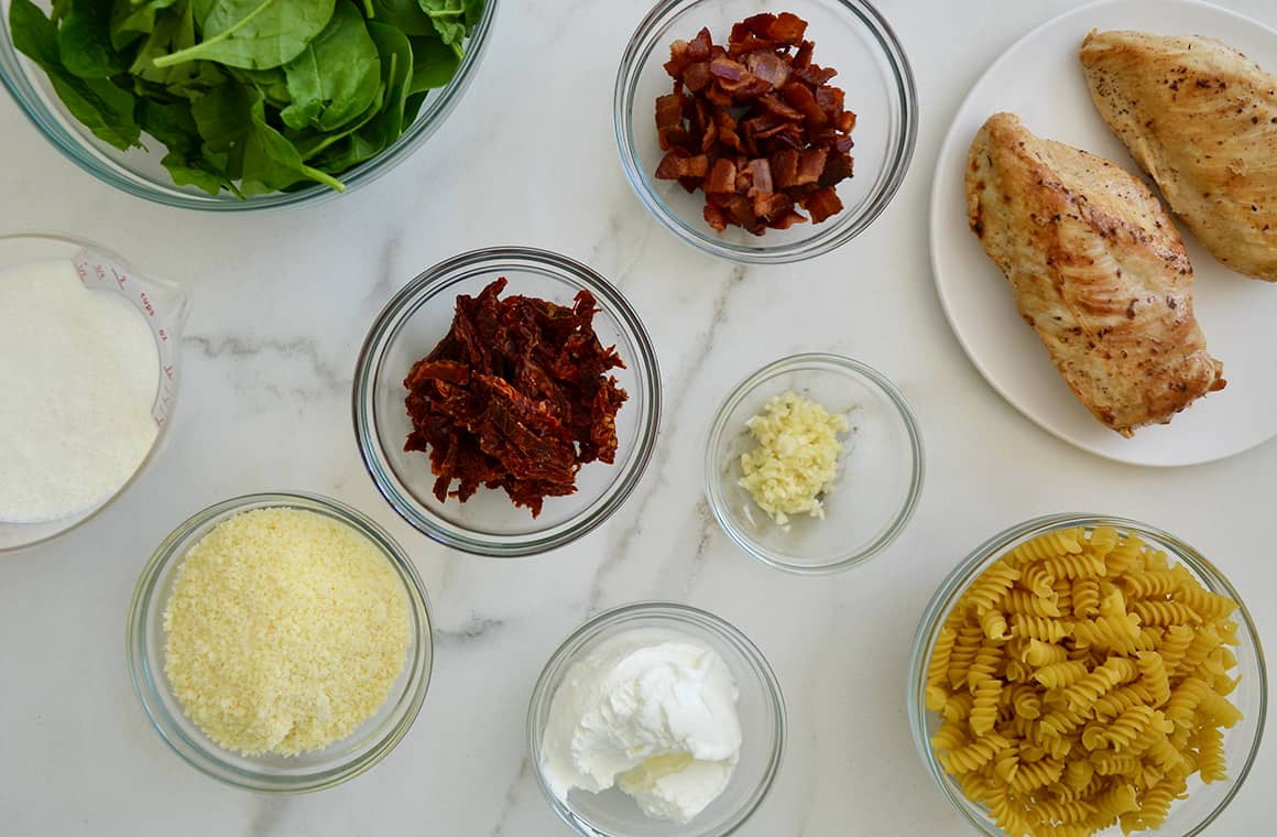 Various sizes of bowls containing spinach, sun dried tomatoes, parmesan cheese, chopped bacon, chicken breasts and minced garlic