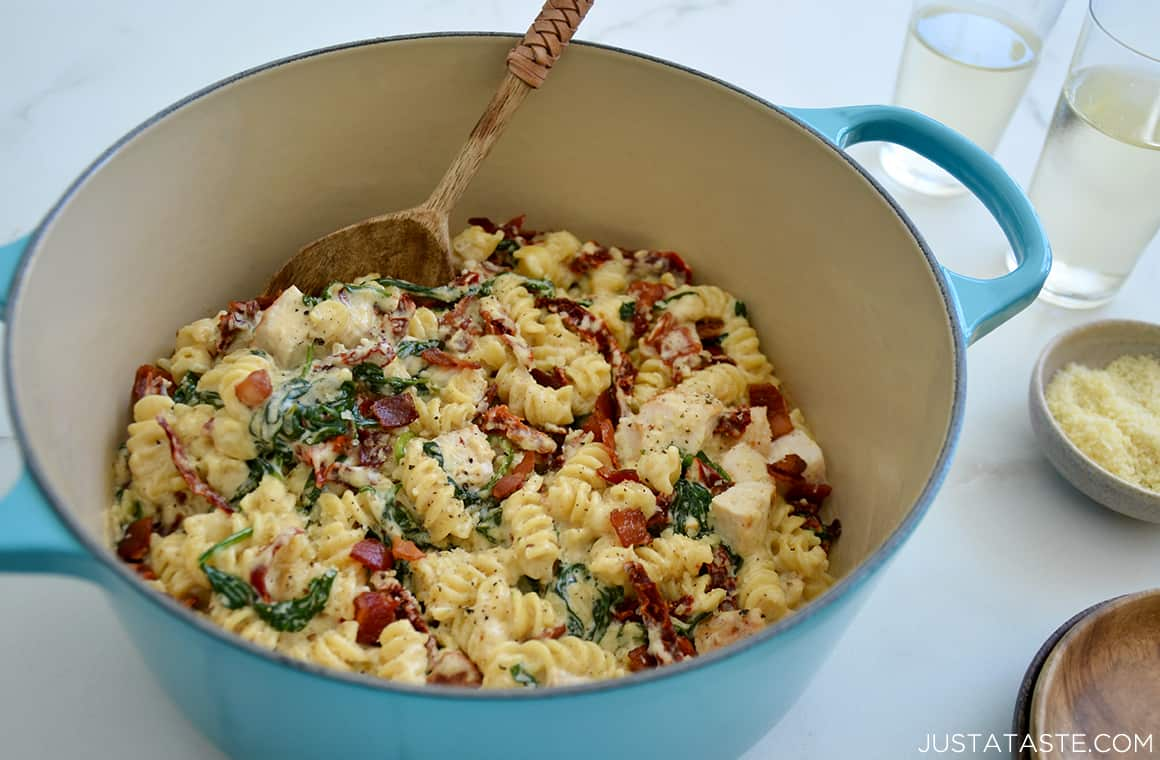 A large pot containing Creamy Tuscan Chicken Pasta and a wooden spoon