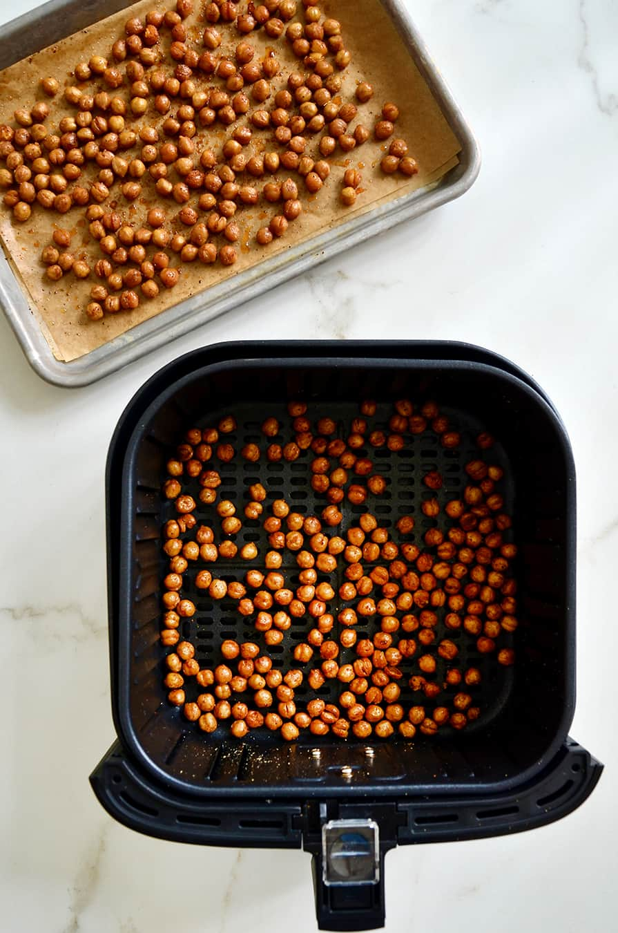 A baking sheet of roasted chickpeas and an air fryer basket