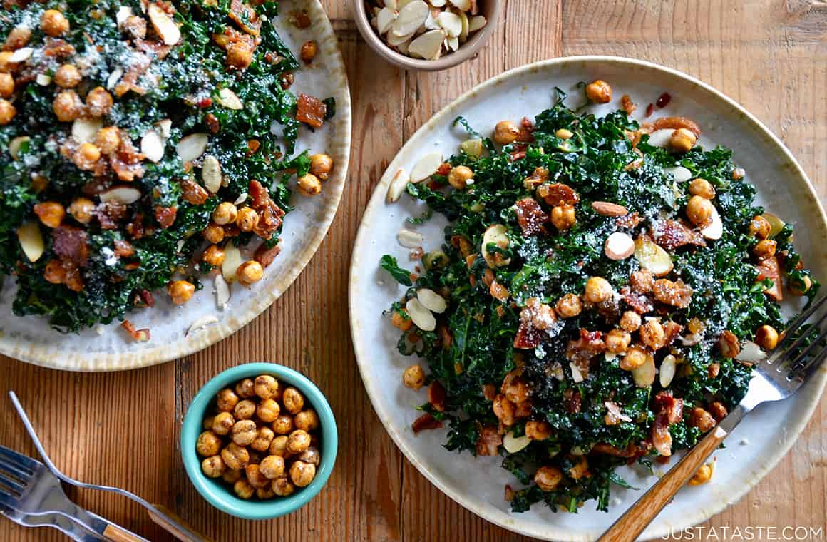 A kale salad on a white plate topped with crispy chickpeas
