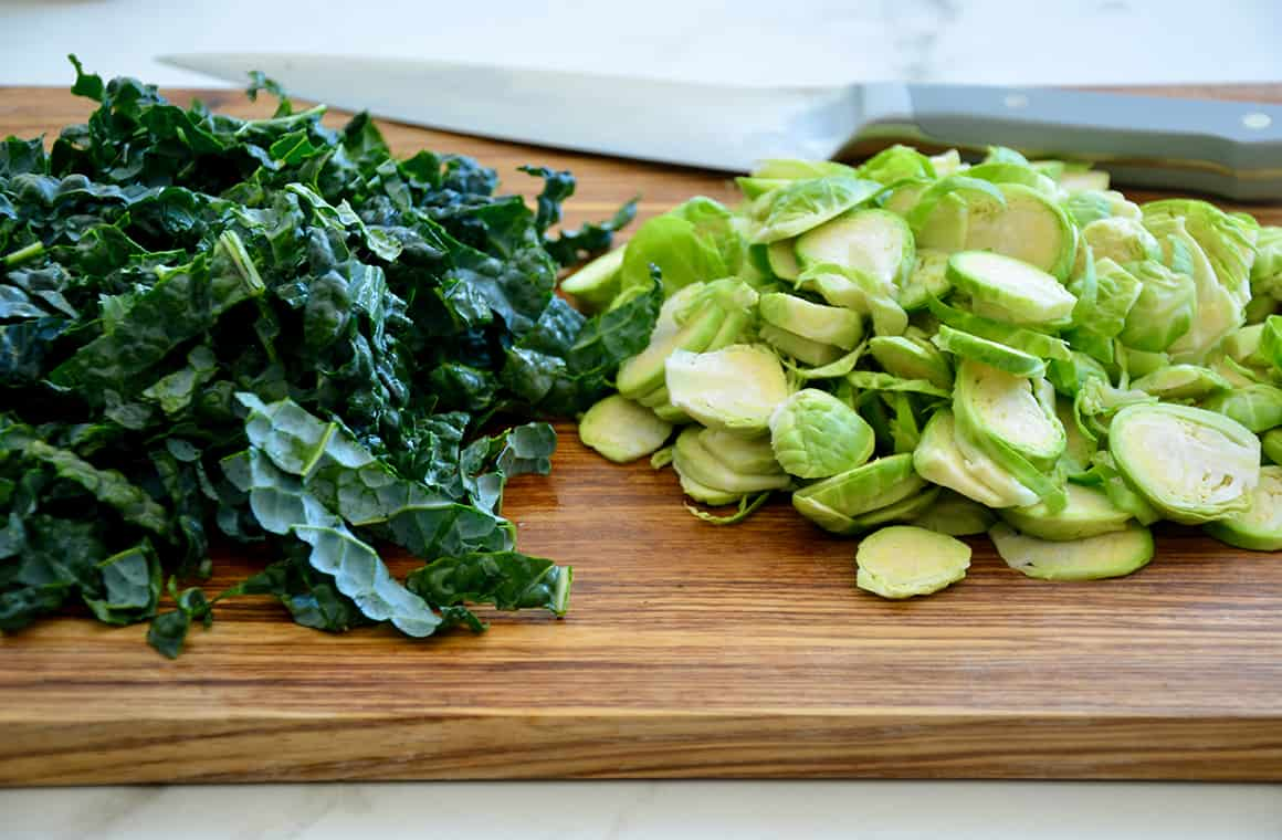Chopped kale and Brussels sprouts on a cutting board with a knife